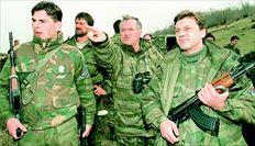 Εναν χρόνο προτού εκδοθεί το διεθνές ένταλµα εις βάρος του, στις 16 Απριλίου του 1994, ο τότε στρατιωτικός ηγέτης των Σερβοβοσνίων, Ράτκο  Μλάντιτς, δείχνει κάτι στους σωµατοφύλακές του, στο Γκόραζντε της Ανατολικής Βοσνίας