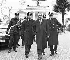 Ο έλληνας πρεσβευτής στη Ρώµη Μιχάλης Καµπάνης (στο κέντρο) συνοδευόµενος από άνδρες της ιταλικής  αστυνοµίας αποχωρεί από την ελληνική πρεσβεία όπου χθες εξουδετερώθηκε δέµα παγιδευµένο µε εκρηκτικά